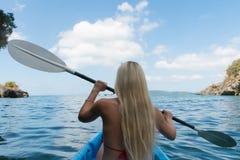 Blond dam i kajaken i det lugna tropiska fj?rdThailand havet royaltyfria bilder