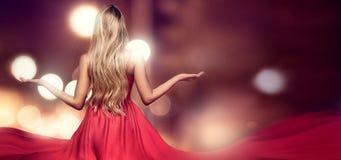 Blond dam i röd elegant maxi klänning royaltyfria foton