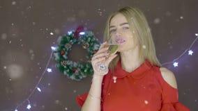 Blond dam i röd klänning med champagneflöjten och maskering på julbakgrunden arkivfilmer
