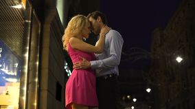 Blond dam som kramar försiktigt hennes älskade man, romantiskt datum i nattcentrum stock video