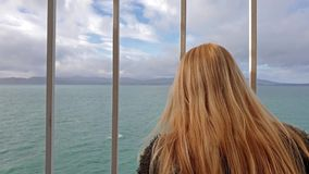 Blond dam som rymmer stängerna och ser till havet och land arkivfilmer