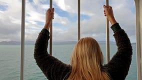 Blond dam som rymmer stängerna och ser till havet och land stock video