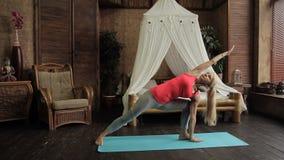 Blond dama trenuje ma joga w ranku w jej sypialni zbiory