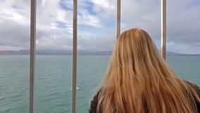 Blond dama trzyma bary i patrzeje morze i ziemia zbiory