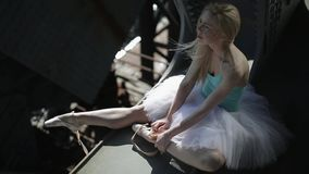 Blond dancer in a white tutu sits on the edge of stock video