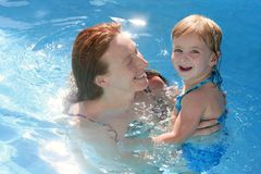 Blond daughter with redhead mother in pool Stock Photos