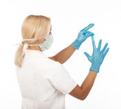 Blond doctor wearing gloves Stock Images