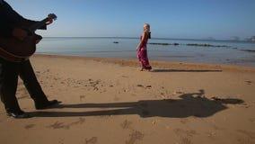Blond droevig meisje in heldere kledingsgangen langs strand stock videobeelden
