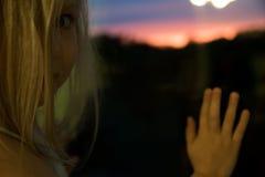 Blond dziewczyn spojrzenia w wieczór okno zdjęcia stock