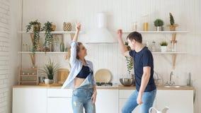 Blond dziewczyna faceta taniec stołową kuchenką w nowożytnej kuchni zdjęcie wideo