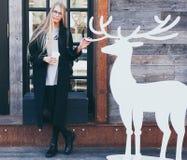 Blond dziewczyna modniś odpoczywa kawę od papierowej filiżanki i pije przy wejściem a w round szkłach z czarnym strojem Zdjęcia Royalty Free