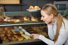 Blond dziewczyna patrzeje w ciasto sklepu wskazywać i okno Fotografia Royalty Free