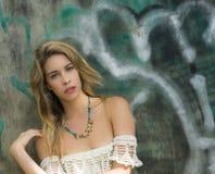 Blond dziewczyna pozuje z graffiti jako tło Zdjęcia Royalty Free