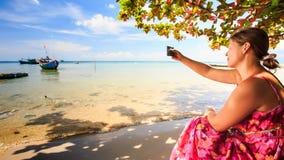 Blond dziewczyna Siedzi na Plażowym Bierze fotografię łodzie w Lazurowym morzu zdjęcie wideo
