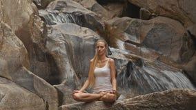 Blond dziewczyna Siedzi w joga pozie Lotus na kamieniu siklawą zdjęcie wideo