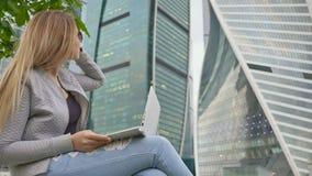 Blond dziewczyna używa białego laptop przeciw tłu wysocy budynki i centrum miasta Dziewczyna w okularach przeciwsłoneczne zbiory wideo