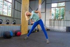 Blond dziewczyna w błękitnych leggings w gym trenuje, stoi, a zdjęcia royalty free