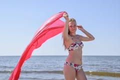 Blond dziewczyna w bikini pozyci na mieniu i plaży czerwona jedwabnicza chusteczka Piękna młoda kobieta w kolorowym bikini na se Fotografia Stock