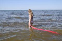 Blond dziewczyna w bikini pozyci na mieniu i plaży czerwona jedwabnicza chusteczka Piękna młoda kobieta w kolorowym bikini na se Obrazy Stock