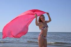 Blond dziewczyna w bikini pozyci na mieniu i plaży czerwona jedwabnicza chusteczka Piękna młoda kobieta w kolorowym bikini na se Zdjęcia Royalty Free