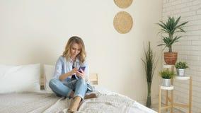 Blond dziewczyna w cajgach siedzi na łóżkowym działaniu na smartphone zbiory