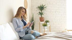 Blond dziewczyna w cajgach siedzi na ? zdjęcie wideo
