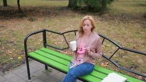 Blond dziewczyna w parkowym łasowaniu pączek Kobieta outdoors żuć słodką babeczkę zdjęcie wideo