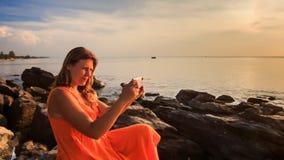 Blond dziewczyna w rewolucjonistce Siedzi na Dennych kamieni Uses Iphone przy zmierzchem zbiory wideo