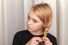 Blond dziewczyna warkoczy plecenie, zbliżenia studia portret Zdjęcie Stock
