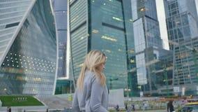 Blond dziewczyna wysyła lotniczego buziaka kamera na tle drapacze chmur i wieżowowie miasto zdjęcie wideo