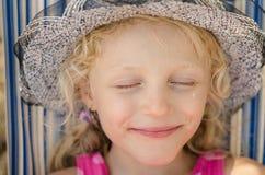 Blond dziewczyna z kapeluszem i zamykającym oko portretem Obrazy Stock