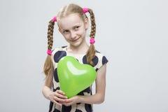 Blond dziewczyna Z Pigtails Pozuje w polki kropki sukni Przeciw bielowi Trzymać Zielonego Lotniczego balon Zdjęcie Royalty Free
