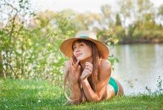 blond dziewczyny trawy kapeluszowi łgarscy potomstwa Fotografia Stock