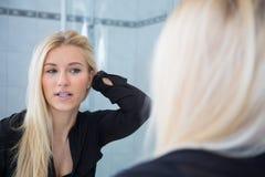Blond in einem Bad mit einem roten Tuch auf dem Kopf Stockfotos