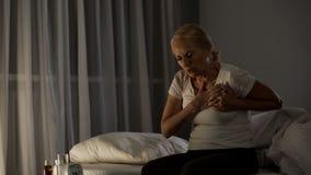Blond elderly female touching chest, feeling sharp pain, cardiac disease infarct royalty free stock images