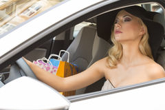 Blond elegant girl driving for shopping Stock Images