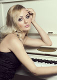 Blond elegant girl near piano Stock Photos