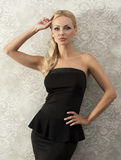 Blond elegant woman near fashion wall Stock Images