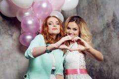 Blond et roux Deux jeunes amies avec du charme à la partie Image libre de droits