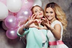 Blond et roux Deux jeunes amies avec du charme à la partie Photographie stock libre de droits