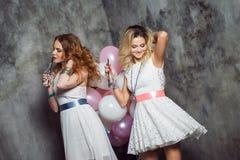 Blond et roux Deux jeunes amies avec du charme à la partie avec des ballons Sur le fond texturisé gris Image stock