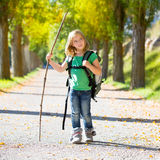 Blond explorer kid girl walking with backpack in autumn trees. Blond explorer kid girl walking with backpack hiking in autumn trees track holding stick stock photos