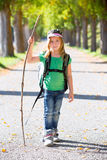 Blond explorer kid girl walking with backpack in autumn trees. Blond explorer kid girl walking with backpack hiking in autumn trees track holding stick stock image
