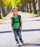 Blond explorer kid girl walking with backpack in autumn trees. Track stock photos