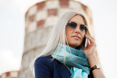 Blond fashion business woman calling on cell phone outdoor. Happy blond fashion business woman calling on cell phone outdoor Royalty Free Stock Photography