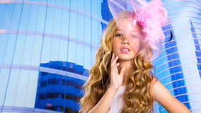 Blond fashion girl with pink hat in blue skyscrapers Stock Images