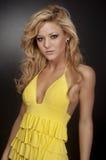 Blond fashion model wearing yellow dress Stock Photos