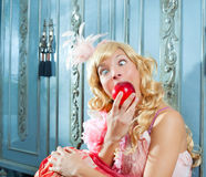 Blond fashion princess eating apple. With funny eyes expression royalty free stock photography