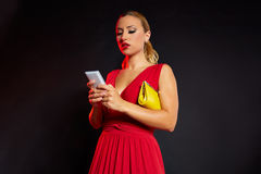 Blond fashion woman in red writing smartphone Royalty Free Stock Image