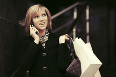 Blond fashion woman with shopping bags calling on cell phone Royalty Free Stock Photo